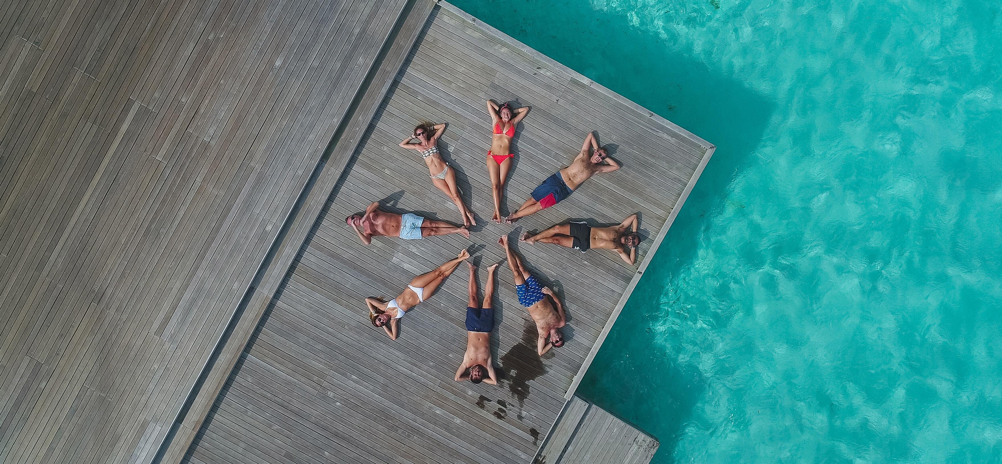 水上コテージで寝そべる男女のグループ